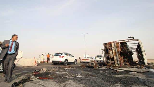 A man walks near the site of suicide car bomb attack on a highway near oilfields in southern Basra,