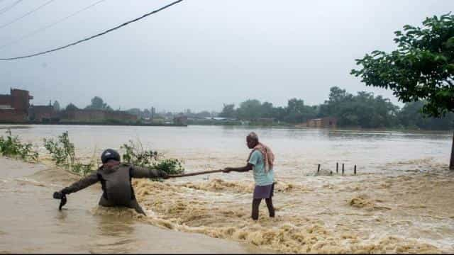 Nepali residents help each other cross a flooded road at Birgunj Parsa district, some 200km south of