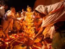 widows light earthen lamps or 'diyas' during Diwali celebrations